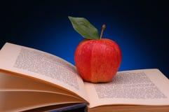 Roter Apple auf geöffnetem Buch Stockfotografie