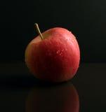 Roter Apple auf schwarzer reflektierender Oberfläche Stockbilder