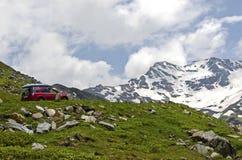 Roter Autoaufstieg die Straße in den Alpen stockfoto