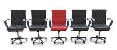 Roter Bürostuhl unter den schwarzen Stühlen lokalisiert auf weißem Hintergrund Stockfoto