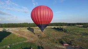 Roter Ballon, der über den Boden gebunden mit den Seilen bereit, das Luftsteigen zu fliegen schwimmt stock video
