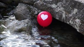 Roter Ballon mit einem weißen Herzen, welches die Meereswellen 4K mit Audio weitergeht stock video footage