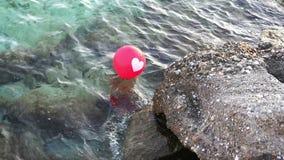 Roter Ballon mit einem weißen Herzen, welches die Wellen 4K mit Audio weitergeht stock video footage