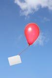 Roter Ballon mit Grußkarte im Himmel Stockfoto