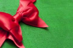 Roter Bandbogen auf grünem Packpapier backround mit Kopienraum stockfoto
