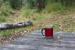 Roter Becher auf einem Holztisch in einem Wald Stockfotografie