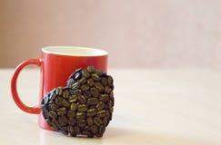 Roter Becher steht auf dem Tisch, nahe dem Becher die Herzform von Kaffeebohnen, ein Symbol der Liebe stockbild