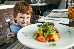 Roter behaarter Junge mit Gabeln Salat essend Stockfoto