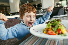Roter behaarter Junge mit Gabeln Salat essend Stockfotos