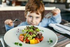 Roter behaarter Junge mit Gabeln Salat essend Stockbild