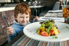 Roter behaarter Junge mit Gabeln Salat essend Lizenzfreie Stockfotos