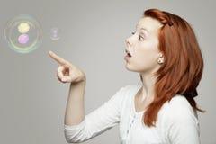 Roter behaarter Mädchenblick zu den Seifenluftblasen und -c$wundern Stockfoto