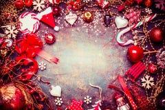 Roter blauer Weihnachtsrahmen mit verschiedenen Weinlesefeiertagsdekorationen und Süßigkeit auf rustikalem Hintergrund Lizenzfreies Stockfoto