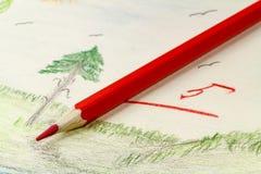 Roter Bleistift auf dem Hintergrund von Kind-` s Zeichnung Lizenzfreies Stockbild
