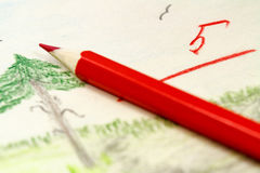 Roter Bleistift auf dem Hintergrund von Kind-` s Zeichnungen mit der Lehrer ` s Einschätzung Lizenzfreie Stockfotos