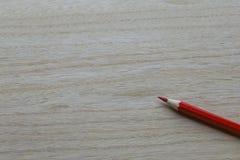 Roter Bleistift auf hölzerner Hintergrundbeschaffenheit lizenzfreies stockbild