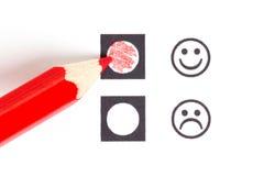 Roter Bleistift, der den rechten smiley wählt stockfotografie