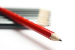 Roter Bleistift, der diagonal graue Gruppe kreuzt Stockfoto