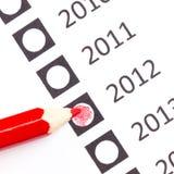 Roter Bleistift, der ein Datum wählt stockbilder