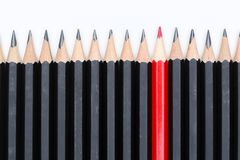 Roter Bleistift, der heraus von der Menge viel identischen schwarzen fel steht Lizenzfreie Stockfotografie