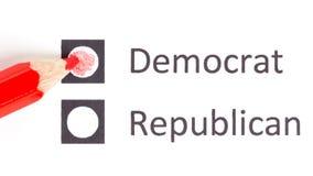 Roter Bleistift, der zwischen Demokraten und Republikaner wählt stockfoto