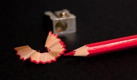 Roter Bleistift mit Bleistiftschnitzeln und Abschluss des Bleistiftspitzers oben Stockfotos