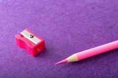 Roter Bleistift mit Bleistiftspitzer auf violettem Hintergrund briefpapier Lizenzfreie Stockfotografie