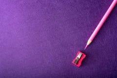 Roter Bleistift mit Bleistiftspitzer auf violettem Hintergrund briefpapier Lizenzfreie Stockfotos