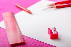 Roter Bleistift mit Bleistiftspitzer, Machthaber und Filzstift auf Weißbuch bedecken Bürowerkzeug Lizenzfreies Stockfoto