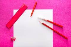 Roter Bleistift mit Bleistiftspitzer, Machthaber und Filzstift auf Weißbuch bedecken Flaches Design briefpapier büro Lizenzfreies Stockfoto