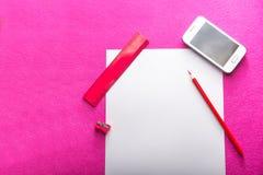Roter Bleistift mit Bleistiftspitzer, Machthaber und Filzstift auf Weißbuch bedecken Weißer Handy Flaches Design briefpapier büro Lizenzfreie Stockfotografie