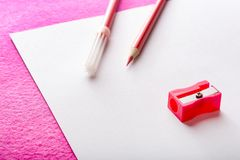Roter Bleistift mit Bleistiftspitzer und roter Filzstift auf Weißbuch bedecken briefpapier Stockfoto