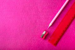 Roter Bleistift mit Bleistiftspitzer und Machthaber auf rotem Hintergrund briefpapier Lizenzfreie Stockfotos
