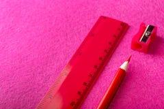 Roter Bleistift mit Bleistiftspitzer und Machthaber auf rotem Hintergrund briefpapier Stockfotografie