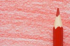 Roter Bleistift mit der Färbung auf einem Papier Stockfotografie