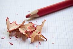 Roter Bleistift und Bleistiftschnitzel auf Notizbuch Stockbild