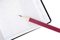 Roter Bleistift und Notizbuch Stockbild