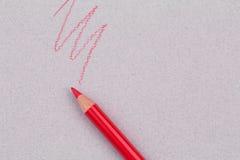 Roter Bleistift und Zickzack zeichnen auf beige Pastellpapiergrobkornschmutzbeschaffenheit Lizenzfreies Stockbild