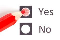 Roter Bleistift zwischen, der ja wählen oder nein stockfotografie