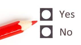 Roter Bleistift zwischen, der ja wählen oder Nr. stockfotografie