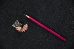 Roter Bleistiftspitzer und geschärfter Abfall stockbild