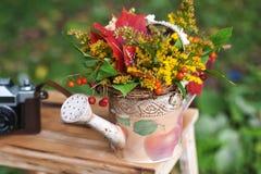 Roter Blumenstrauß des Herbstes von Ahornblättern im Wasserkanister Lizenzfreie Stockfotos