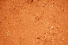Roter Bodenbeschaffenheitshintergrund, getrockneter Lehm Stockbild