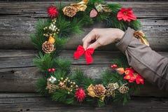 Roter Bogen im menschlichen Arm an der grauen hölzernen Blockhauswand mit Weihnachtskranz Stockbild