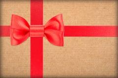 Eingewickeltes Weinlesegeschenk mit rotem Bogen lizenzfreie stockfotos
