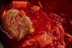 Roter Borschtsch machte vom beetrot, vom Gemüse und vom Fleisch mit Sahne in einem Schwarzblech auf einem kupfernen Hintergrund lizenzfreie stockfotografie