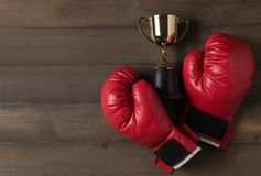 Roter Boxhandschuh und Trophäe auf hölzernem bcakground lizenzfreie stockfotos