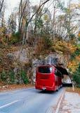 Roter Bus auf Straße am Tunnel in den Bergen, in geblutet stockfoto
