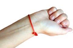 Roter Faden gebunden am Handgelenk als Charme lizenzfreies stockfoto