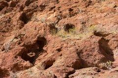 Roter Felsenhintergrund des abgefressenen Vulkanbergs Stockbild